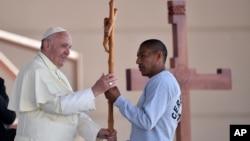Paus Fransiskus menerima sebuah salib yang dibuat oleh narapidana saat mengunjungi penjara di Ciudad Juarez, Meksiko hari Rabu (17/2).