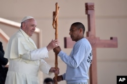 Pope Francis receives a cross made by an inmate at the CeReSo No. 3 prison in Ciudad Juarez, Mexico, Feb. 17, 2016.