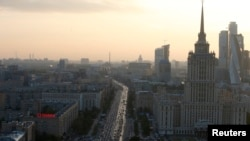 Vehicles move along a road near the buildings of the Moscow International Business Centre (R, back) in Moscow, Sept. 17, 2014.