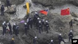 手持中國和台灣旗子的活動人士8月15日登上釣魚島後被日本警察逮捕