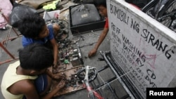 Children recover copper and other metals from discarded televisions and other electronic waste, which they exchange for money from nearby junkshops, along a road in Manila April 7, 2011. An e-waste recycling and reclamation company salvages gold and other