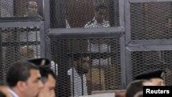 Para terdakwa di belakang jeruji besi dalam pengadilan di Mesir (18/6) atas tuduhan membunuh Mayjen Nabil Faraq.