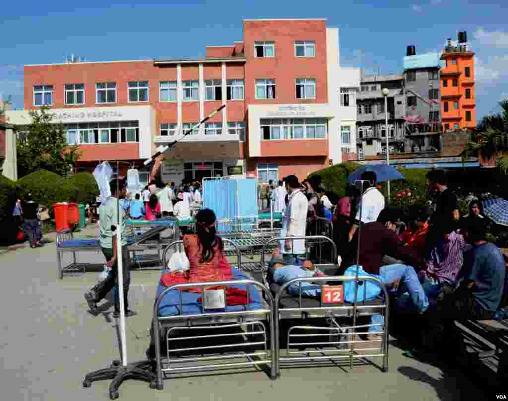 Patients, some still in their hospital beds, wait outside Teaching Hospital, Kathmandu, May 12, 2015. (Photo: Bikas Rauniar for VOA)