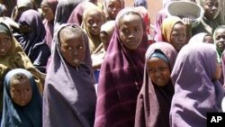 Internally displaced Somali children line up with containers in hand to receive food aid at a food distribution center, in Mogadishu, Somalia, (File Photo - March 15, 2011)