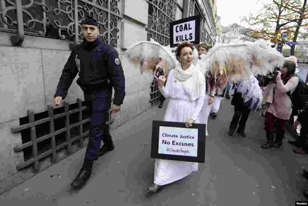 Seorang polisi Perancis mengawal aktivis lingkungan Australia yang disebut Climate Guardian Angels saat melakukan demo di Konferensi Perubahan Iklim 2015 (COP21) di Paris.