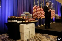 FILE - A secret service agent stands on the stage prior to a scheduled news conference by Republican presidential candidate Donald Trump in Jupiter, Fla., March 8, 2016. At left is a display of Trump-branded wine, water and steaks.