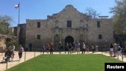 Visitors walk at the entrance to the Alamo, the most-visited tourist site in the state, in San Antonio, Texas, March 2, 2015.