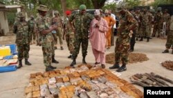 Officials stand near ammunition seized from suspected members of Hezbollah after raid of building in Kano, Nigeria, May 30, 2012