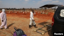 Funeral workers wearing personal protective equipment are seen after a burial South Africa