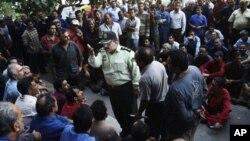 지난 8월 이란 산업부 건물 앞에서 임금 체불에 항의하며 벌어진 노동자들의 시위 중, 경찰 간부(가운데) 해산을 요구하고 있다. (자료 사진)