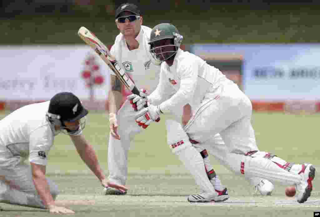 Zimbabwe's batsman Tatenda Taibu (R) plays a shot, as New Zealand's Doug Bracewell (L) and Brendon McCullum watch, during the third day of their test cricket match in Bulawayo November 3, 2011. REUTERS/Philimon Bulawayo (ZIMBABWE - Tags: SPORT CRICKET)