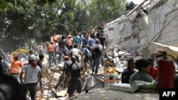 People remove debris of a collapsed building looking for possible victims after a quake rattled Mexico City, Sept. 19, 2017.