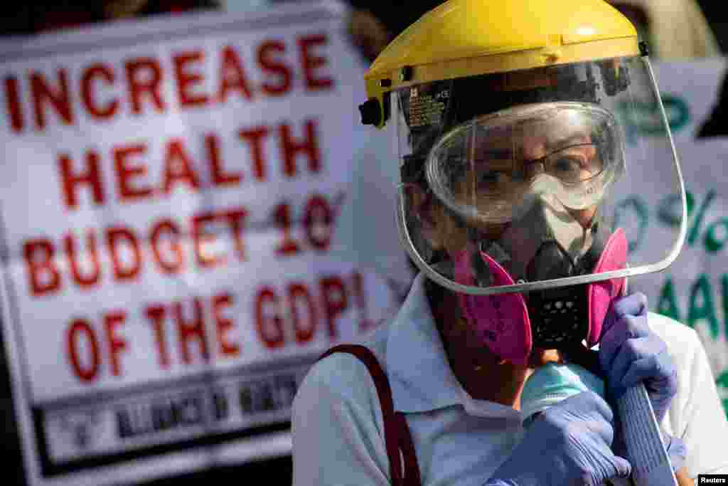 A health worker joins a protest calling for better government response amid the coronavirus outbreak, as the one-year anniversary of the first COVID-19 case in the Philippines approaches, outside a government hospital in Quezon City, Metro Manila, Philipp