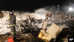 Para petugas pemadam kebakaran dan Tim SAR memeriksa lokasi jatuhnya pesawat penumpang Boeing 737 milik Maskapai Penerbangan Tatarstan di dekat Kaza, 720 kilometer dari Moskow (17/11).