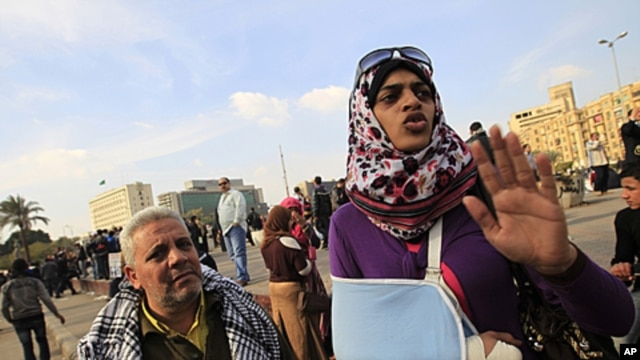 A female Egyptian protester wearing a sling to support her arm, describes how she was hit by Egyptian army soldiers, during a demonstration against the military regime, at Tahrir Square in central Cairo, December 21, 2011.