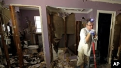 Edward Woods takes a break from cleaning up his mother's home, which was destroyed by floodwaters in the aftermath of Hurricane Harvey, Sunday, Sept. 3, 2017, in Spring, Texas.