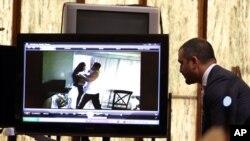 Avocat de la défense, Saam Zangeneh, à droite, regarde une vidéo d'une dispute entre Jennifer Alfonso, la victime assassinée, et l'accusé Derek Medina prise par une vidéo de surveillance de la maison en 2012 lors du procès de Medina, 17 novembre 2015 à Miami.
