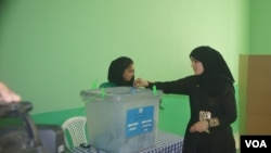 Seorang warga Afghanistan memasukkan surat suaranya ke dalam kotak di sebuah TPS di wilayah Mazar-e-Sharif. Meski diancam serangan Taliban, warga Afghanistan mendatangi TPS-TPS untuk memilih presiden baru negara itu, Sabtu (14/6).