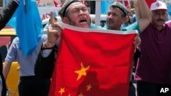 ARSIP – Foto warga Uighur yang tinggal di Turki bersama warga Turki pendukungnya meneriakkan slogan-slogan seraya mengangkat bendera China sebelum membakarnya dalam sebuah unjuk rasa di dekat konsulat China di Istanbul (foto: AP Photo/Lefteris Pitarakis, Arsip)