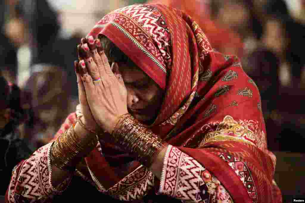 A woman prays during a Christmas service at the Sacred Heart Cathedral in Lahore, Pakistan, Dec. 25, 2018.