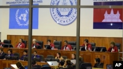 FILE - Extraordinary Chambers in the Courts of Cambodia, court officers of the U.N.-backed war crimes tribunal are seen through windows during a hearing of former Khmer Rouge top leaders in Phnom Penh.