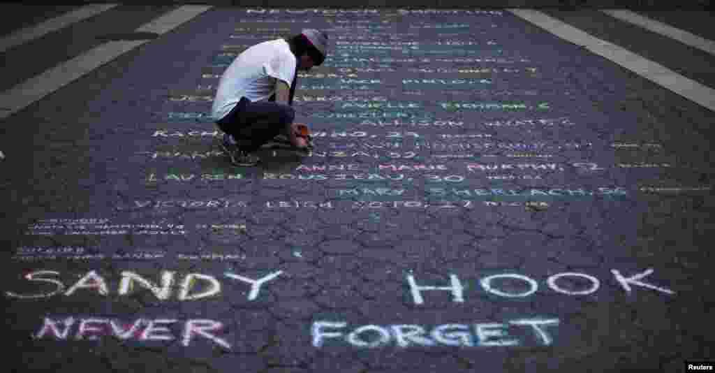 A Union Square, à New York, l'artiste de rue Mark Panzarino, écrit les noms des victimes de l'école élémentaire Sandy Hook ou un homme armé a tué 28 personnes, le 14 décembre 2012.