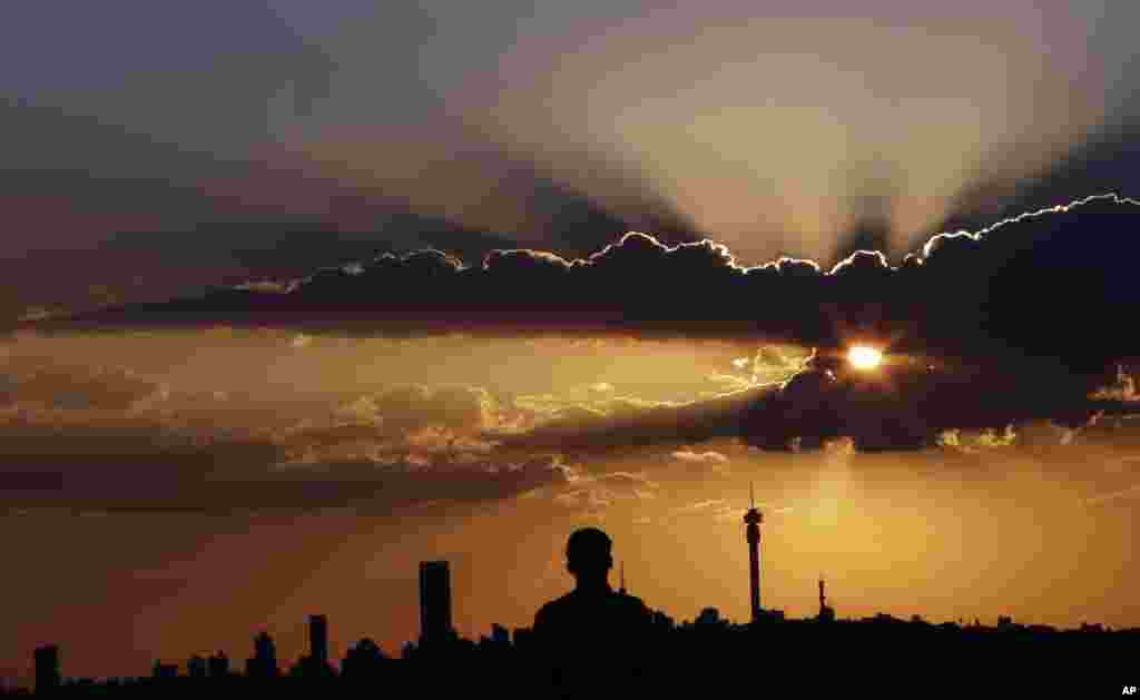 A man watches the sun set against the skyline in Johannesburg, South Africa, March. 10, 2015.
