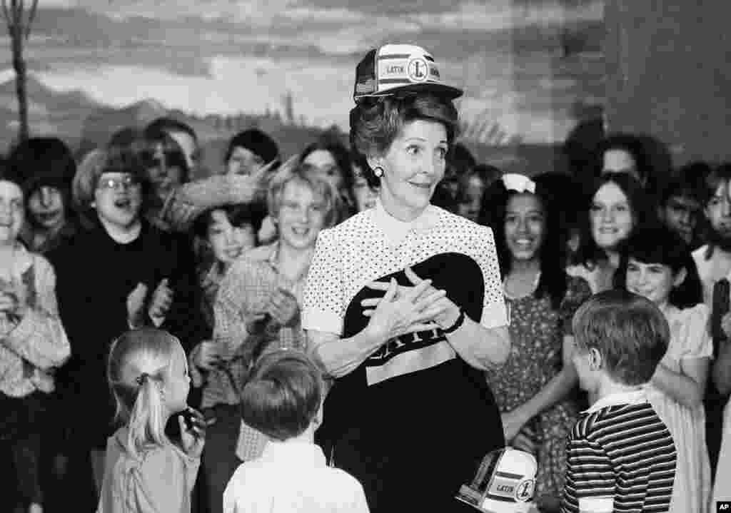 លោកស្រី Nancy Reagan ជាភរិយាប្រធានាធិបតីអាមេរិក បង្ហាញម៉ូតមួក និងអាវសម្រាប់សិស្សសាលា នៅពេលដែលលោកស្រីបានធ្វើដំណើរទស្សនកិច្ចទៅកាន់សាលារៀន Latin School នៅទីក្រុង Chicago កាលពីថ្ងៃទី១៤ ខែឧសភា ឆ្នាំ១៩៨២។