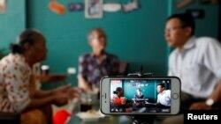 Nhà hoạt động Lê Văn Dũng (phải) truyền trực tiếp qua Facebook tại một quán cà phê ở Hà Nội