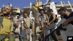 反政府武装战士在阿齐齐亚区官邸大院内脚踏卡扎菲像