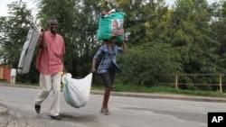 Burundians carry their belongings in Bujumbura, Burundi, Nov. 7, 2015. Carrying their prized possessions, scores of people have fled Burundi's capital before a security crackdown.