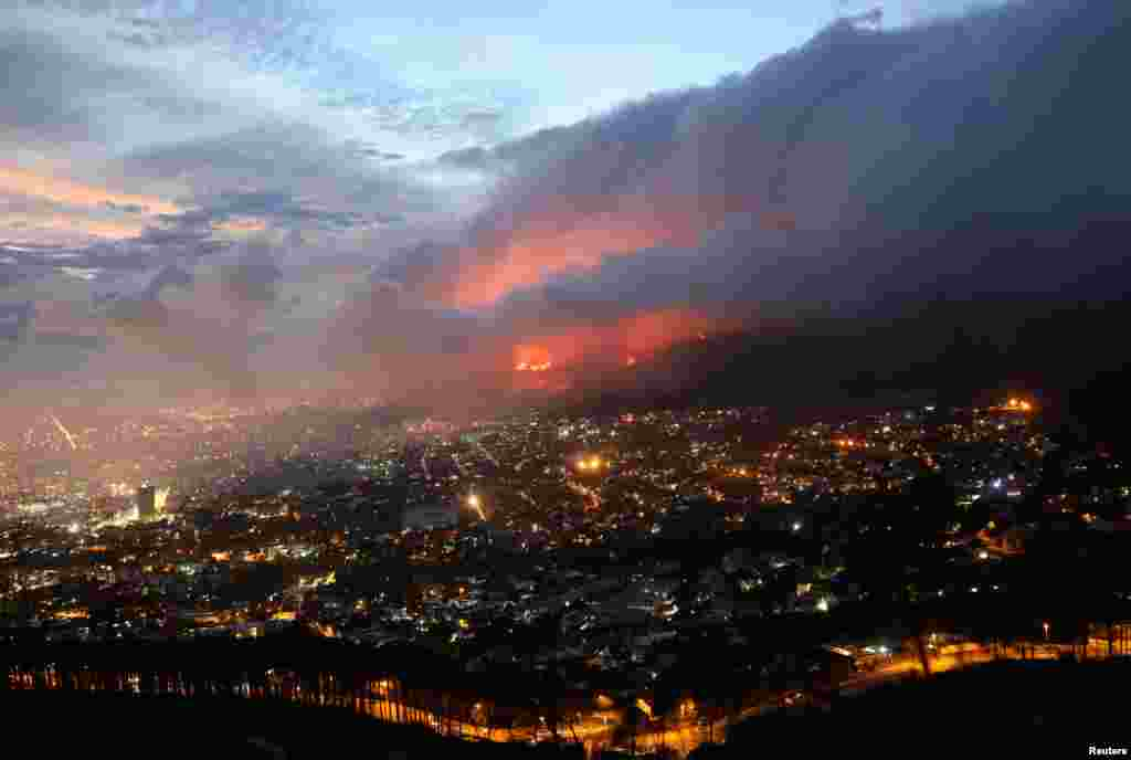 Flames are seen close to the city fanned by strong winds after a bushfire broke out on the slopes of Table Mountain in Cape Town, South Africa.