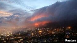 Des flammes sont attisées par des vents violents après qu'un feu de brousse se soit déclaré sur les pentes de la Table Mountain au Cap, en Afrique du Sud, le 19 avril 2021.