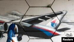 FILE - A woman walks past graffiti of Flight MH370 in Kuala Lumpur.