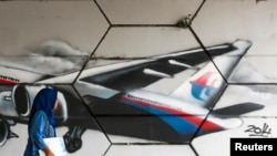FILE - A woman walks past graffiti of Flight MH370 in Kuala Lumpur.