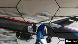Seorang perempuan melewati gambar grafiti pesawat MH370 di Kuala Lumpur (Foto: dok).