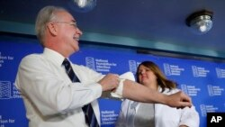 Health and Human Services Secretary Tom Price (L) rolls-up his sleeve before receiving a flu shot from Sharon Walsh-Bonadies, RN. (R), during a news conference in Washington, Sept. 28, 2017.