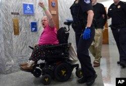Una manifestante en silla de ruedas protesta contra la propuesta de salud republicana en el Congreso de EE.UU. mientras la policía del Capitolio, la retira de la sala donde senadores revisaban la medida. Sept. 25, 2017.