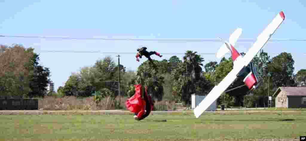This photo released by the Polk County Sheriff's Office shows a plane nose-diving into the ground after getting tangled with a parachutist, at the South Lakeland Airport in Mulberry, Florida, Both the pilot and jumper were hospitalized with minor injuries, March 8, 2014.