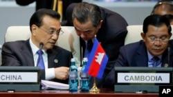 中国总理李克强在出席亚欧峰会期间与中国外长王毅交谈,李克强邻座为柬埔寨首相洪森。(2016年7月15日)