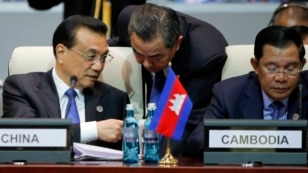 Chinese Premier Li Keqiang, left, talks with Foreign Minister Wang Yi, center, as he and Cambodia's Prime Minister Hun Sen, right, attend the opening session of the Asia-Europe Meeting summit in Ulaanbaatar, Mongolia, July 15, 2016.