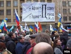 莫斯科2014年3月反对吞并克里米亚的一场示威中,一名示威者手举标语,1980莫斯科奥运会后,苏联入侵阿富汗,接下来苏联解体,俄罗斯入侵乌克兰也会造成独裁和混乱。(美国之音白桦拍摄)