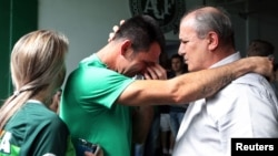 Chapecoense goalkeeper Jose Nivaldo, left, reacts as he talks with Jose Tozzi, who became the team's acting president when his predecessor died in the crash in Chapeco, Brazil, Nov. 30, 2016.
