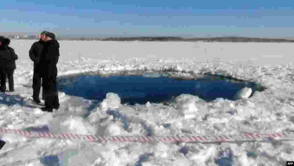Warga berdiri dekat lubang berdiameter enam meter pada danau yang membeku, tempat jatuhnya meteor di luar kota Chebakul di wilayah Chelyabinsk. (Foto: Kepolisian Chelyabinsk)