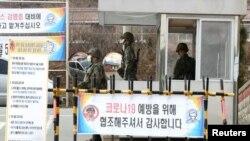Tentara Korea Selatan mengenakan masker untuk mencegah penularan virus corona, saat bertugas di pos pemeriksaan pangkalan militer di Daegu, Korea Selatan, 26 Februari 2020. (Yonhap via REUTERS)