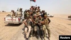 Milisi Syiah yang membantu pasukan Irak menaiki kendaraan militer di provinsi Anbar (26/5).