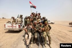 Iraq's Shi'ite paramilitaries ride in military vehicles in Nibai, May 26, 2015.