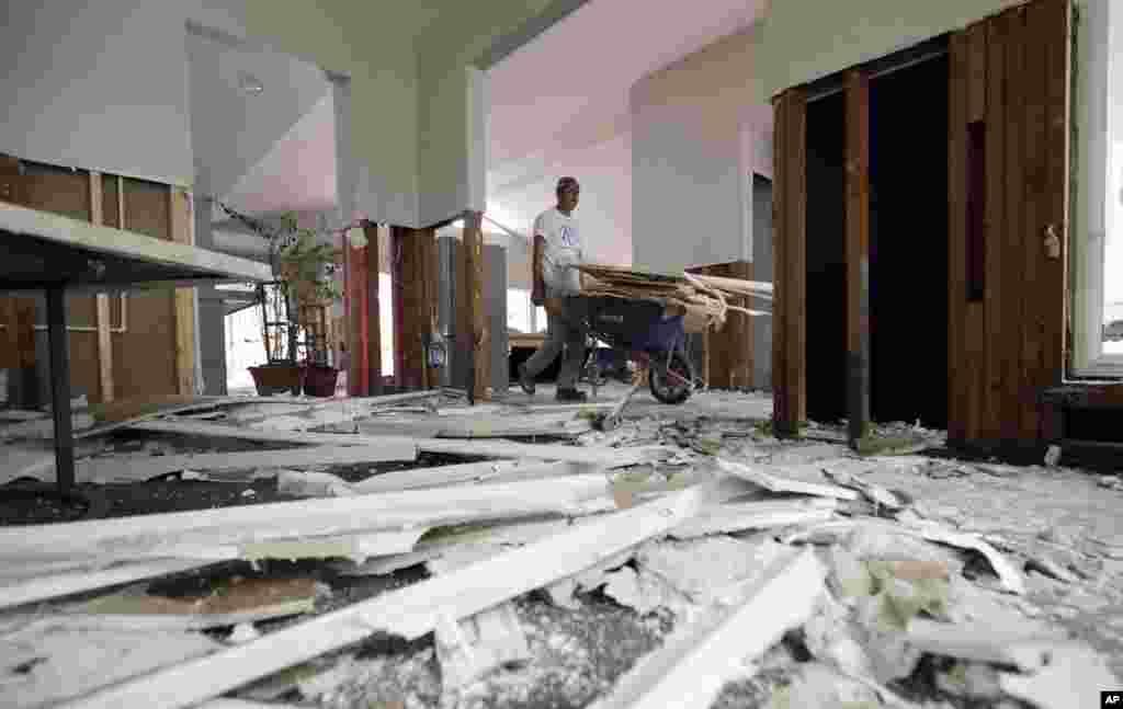 José Martínez, remueve los restos de una pared derribada en una casa dañada por las inundaciones de la tormenta tropical Harvey, en Houston, Texas. Foto AP.