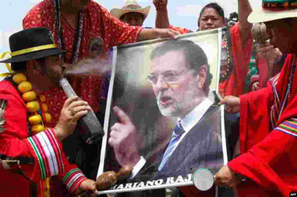 A shaman spits flowered water on a poster of Spain's Prime Minister Mariano Rajoy during a ritual for good luck in 2012 in Lima, Peru, Thursday Dec. 29, 2011. (AP Photo/Karel Navarro)