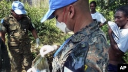 UN peacekeepers from Guatemala take a sample of excrement next to the Nepali UN base in Mirebalais, 27 Oct 2010. UN investigators took samples of foul-smelling waste flowing persistent accusations that excrement from a Nepalese peacekeeping base caused t